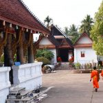monks walking in the front yard of Wat Aham, Laos Vacations