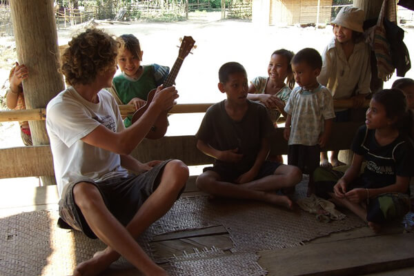 Traveler-playing-with-local-children-in-ethnic, Luang Prabang tour