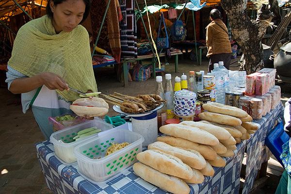 A street vendor makes Khao Jii Paté lao cuisine
